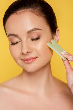 portrait of beautiful woman with closed eyes facial jade gua sha isolated on yellow