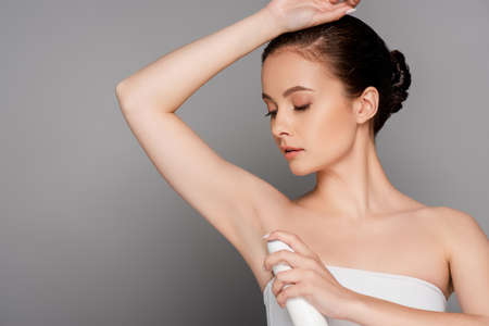 beautiful brunette woman holding deodorant near armpit isolated on gray