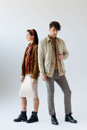 Full length view of stylish man in autumn outfit looking at camera, standing near attractive woman looking away on gray
