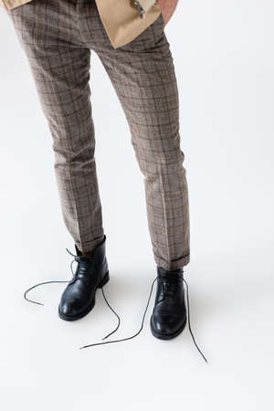 partial view of male legs in fashionable trousers and unlaced black boots on white