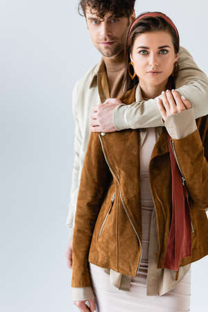 handsome man hugging stylish woman in suede jacket isolated on gray