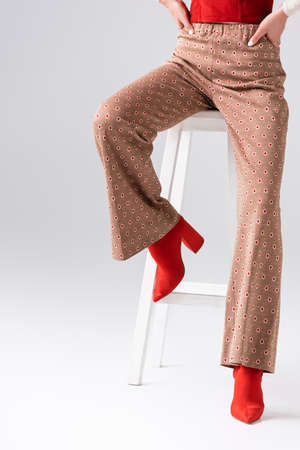 cropped view of trendy girl in red boots and beige trousers sitting on stool on gray