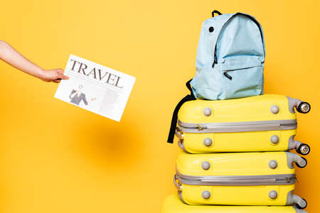 cropped view of woman holding travel newspaper near blue backpack on travel bags on yellow Banque d'images