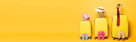 family travel bags with beach summer accessories isolated on yellow, panoramic shot Foto de archivo