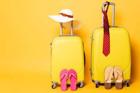 travel bags with male and female accessories isolated on yellow Foto de archivo