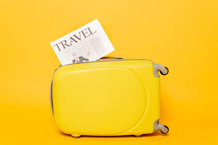 travel newspaper on colorful suitcase on yellow background