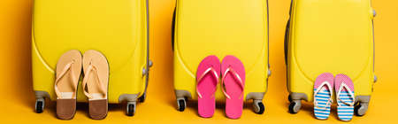 travel bags with family flip flops isolated on yellow, panoramic shot Foto de archivo