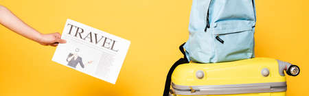 cropped view of woman holding travel newspaper near blue backpack on travel bag on yellow, panoramic shot