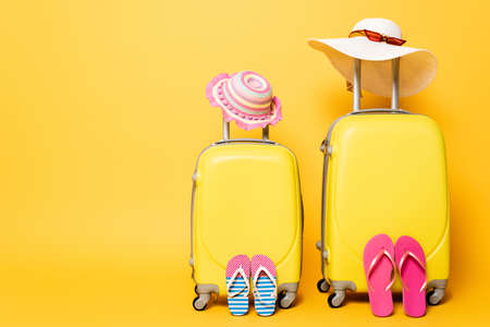 mother and daughter travel bags with flip flops, sun hats and sunglasses isolated on yellow