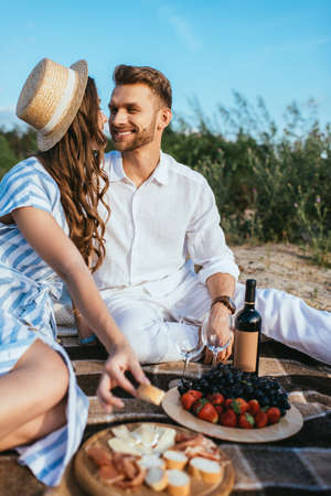 selective focus of happy couple sitting near tasty food and bottle with wine
