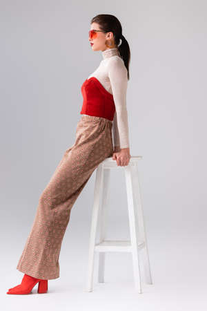 side view of fashionable girl in beige trousers and red corset on turtleneck leaning on stool on gray