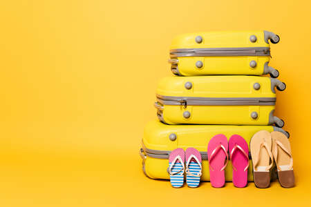 travel bags with family flip flops isolated on yellow Foto de archivo