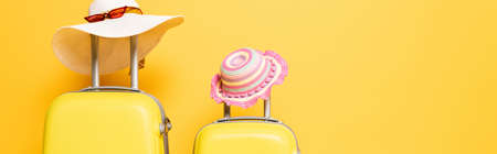 mother and daughter travel bags with sun hats and sunglasses isolated on yellow, panoramic shot
