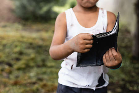 Cropped view of poor arfican american boy holding wallet on urban street