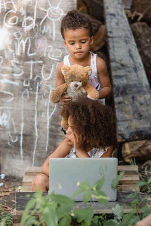 Selective focus of dirty african american kids with laptop and teddy bear on urban street