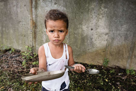 Dissatisfied african american boy holding dirty plate and spoon and looking at camera on urban street Stock Photo