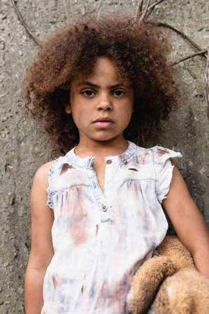 Destitute african american child holding messy teddy bear and looking at camera on urban street