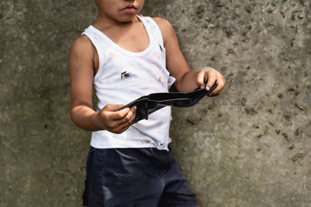 Cropped view of beggar african american child holding wallet near concrete wall on urban street Stock Photo