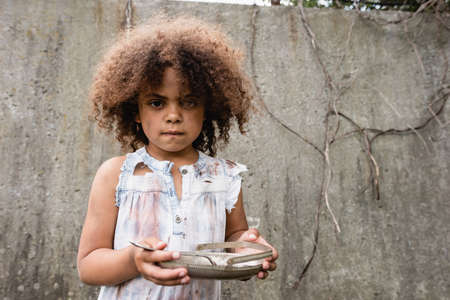Selective focus of african american kid with messy face holding metal plate and spoon on urban street Stock Photo