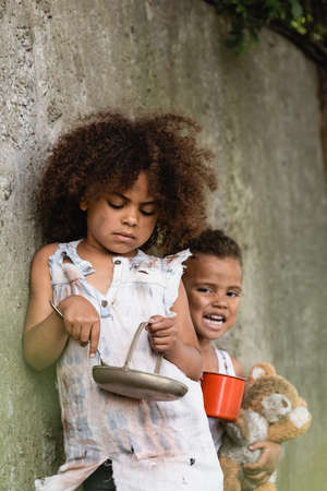 Selective focus of poor african american kid holding metal spoon and plate near brother begging alms in slum