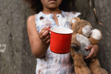 Cropped view of poor african american kid holding metal cup and teddy bear while begging alms on urban street