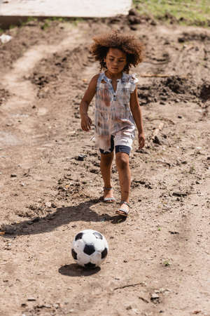Selective focus of poor african american child playing football on dirty road on urban street