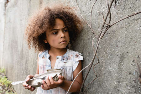 Selective focus of poor african american kid holding dirty metal plate and spoon near concrete wall on urban street Zdjęcie Seryjne