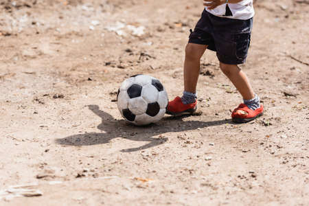 Cropped view of poor african american boy playing with soccer ball on dirty road on urban street