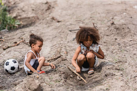 Poor african american kids playing on dirty road near football in slum Imagens