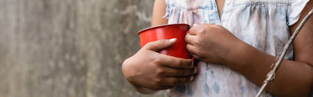 Panoramic crop of poor african american child holding metal cup on urban street