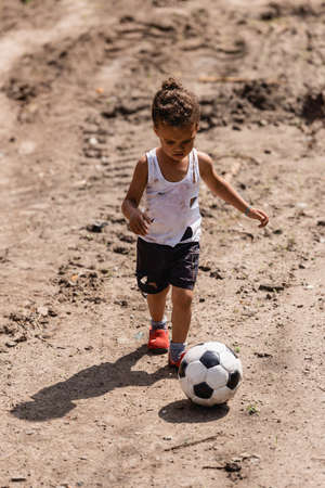 Poor african american boy playing football on dirty road on urban street