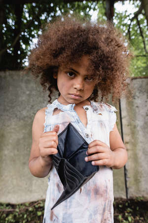 Selective focus of african american child in dirty clothes holding empty wallet and looking at camera on urban street