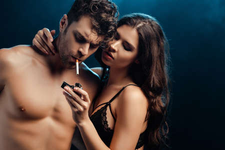 Sexy woman in bra holding lighter and embracing boyfriend with cigarette on black background