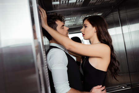 Selective focus of handsome man hugging sexy girlfriend in elevator Banque d'images