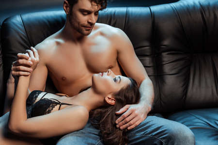 Shirtless man holding hand of beautiful girl in lace bra on couch on black background
