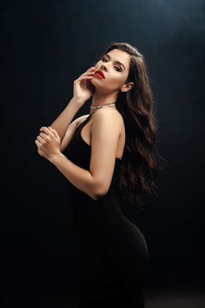 sexy woman in black dress looking at camera on black background