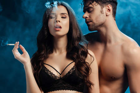 Sexy girl in lace bra smoking cigarette near shirtless man on black background with smoke