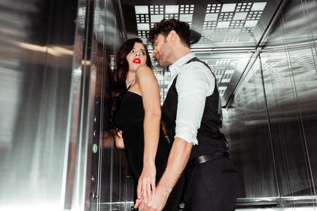 Selective focus of handsome man touching beautiful woman in elevator