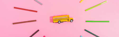 top view of school bus model framed with color felt tip pens on pink, horizontal image
