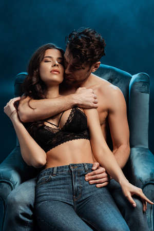 Shirtless man embracing girlfriend in bra and jeans on armchair on black background with smoke