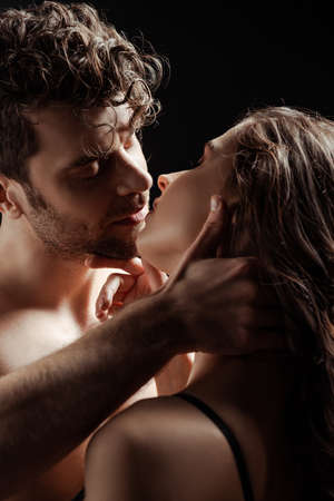 Shirtless man kissing and touching brunette girlfriend isolated on black