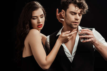 Beautiful woman with red lips touching boyfriend with glass of whiskey isolated on black