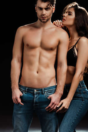 Sensual girl in bra and jeans standing near handsome shirtless man on black background