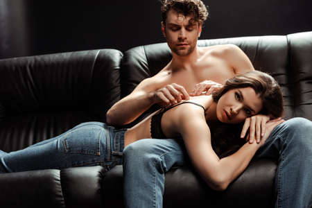 Shirtless man in jeans touching back of sensual woman on couch on black background