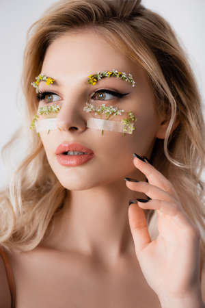 beautiful blonde woman with wildflowers under eyes looking away isolated on white