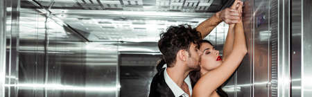 Horizontal crop of young man kissing beautiful girlfriend in elevator