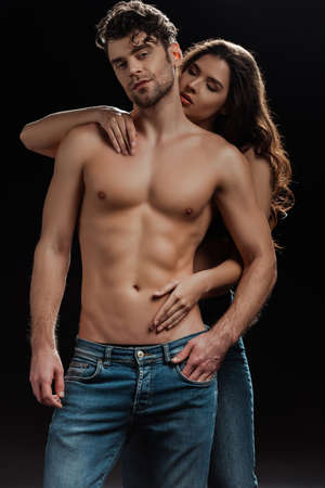 Attractive girl touching torso of muscular man looking at camera isolated on black