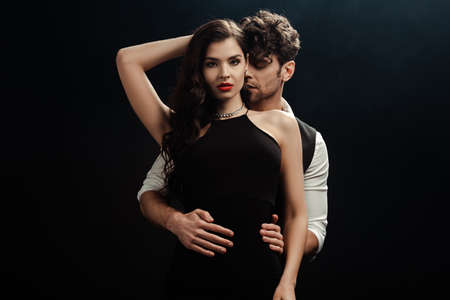 Handsome man hugging beautiful woman with red lips isolated on black Banque d'images
