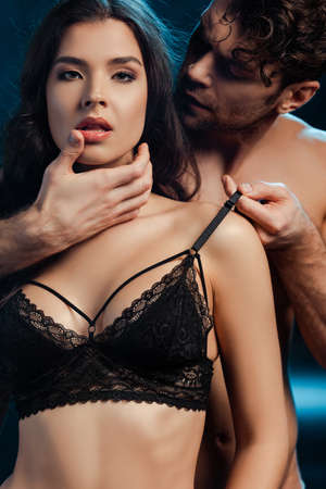 Muscular man touching face and bra of beautiful girl looking at camera on black background Banque d'images