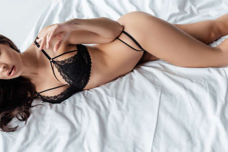 Cropped view of seductive girl touching bra while lying on bed Banque d'images